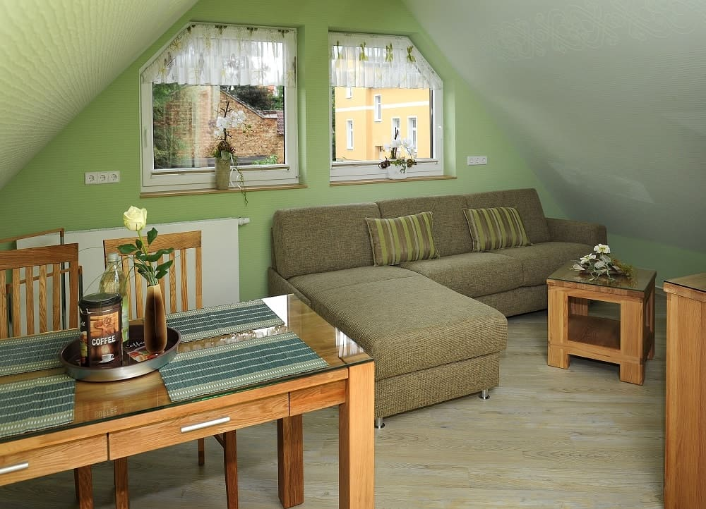 Der Wohn- und Essbereich im Apartment Stadtblick mit einer schönen Couch und Holzmöbeln