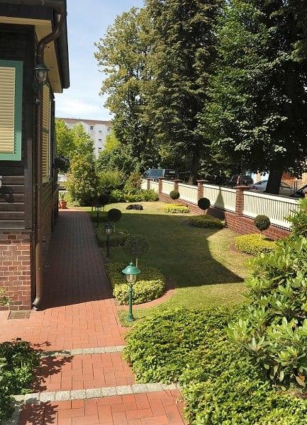 Der Aussenbereich der Apartments mit kleine Gehweg und schön gestalteter Rasenanalge